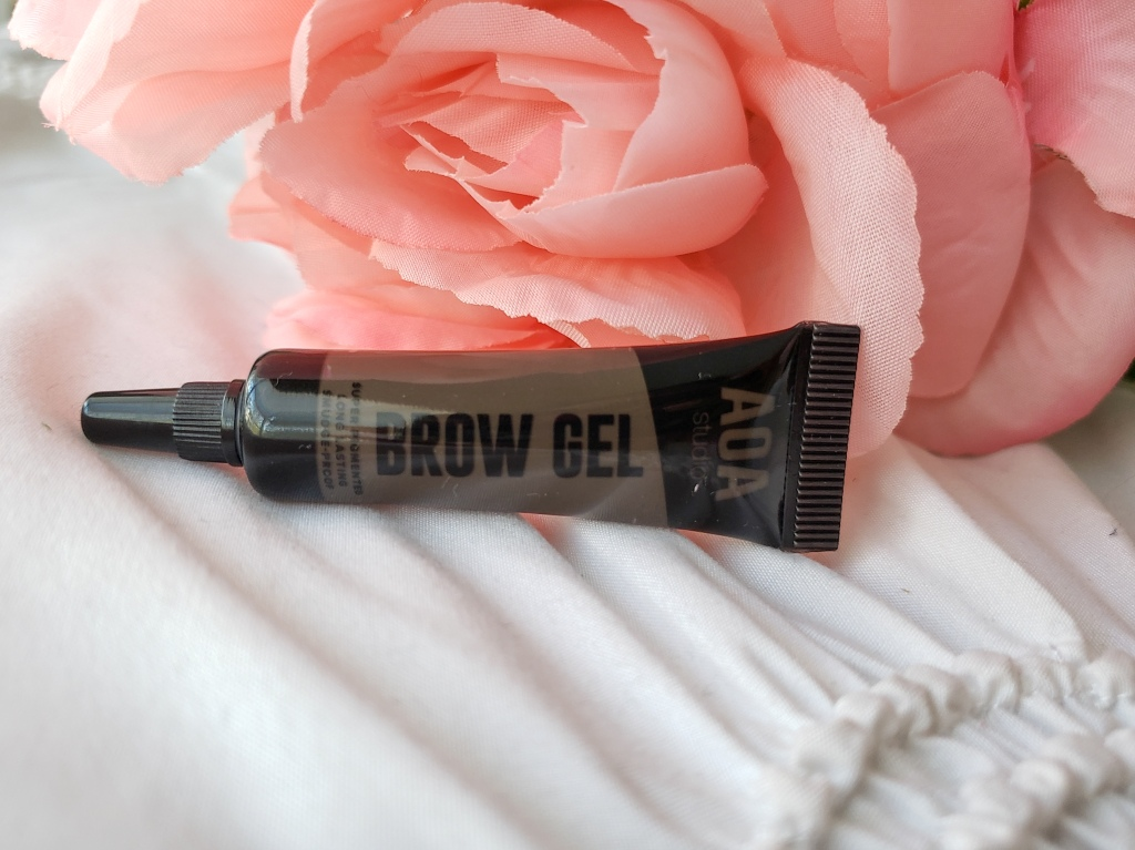 A small tube of dark brown AOA Brow Gal is learning against a pink rose.