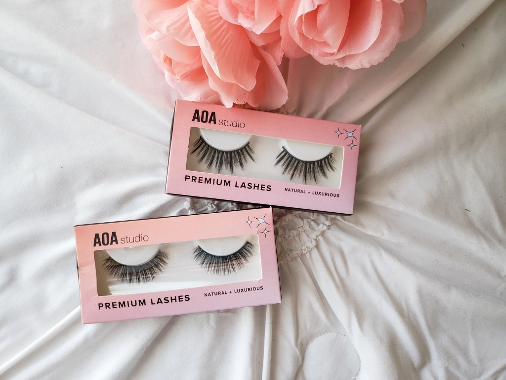Two pairs of AOA studio 3D Faux Mink Lashes are on a bed with a flower in the background.