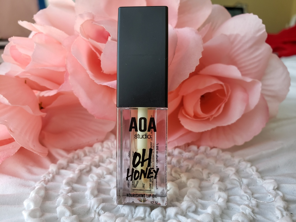A small tube of AOA Studio Oh Honey Lip Oil is standing up on a white bed with pink roses in the background.