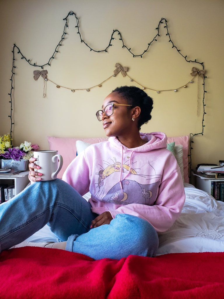 A young woman is sitting on a bed wearing a pastel pink screen printed Sailor Moon hoodie from Kero and Luna and holding a cup of tea.