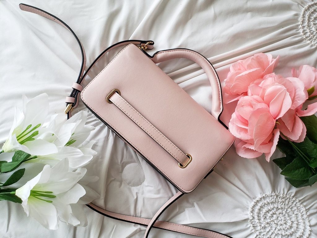 A pastel pink crossbody handbag from A New Day is lying on a white bedspread with flowers.